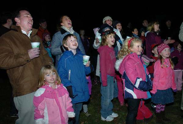 West Newbury: Residents cheer at the West Newbury Christmas tree is lit after a technical glitch forced four countdowns before the lights illuminated. Bryan Eaton/Staff Photo