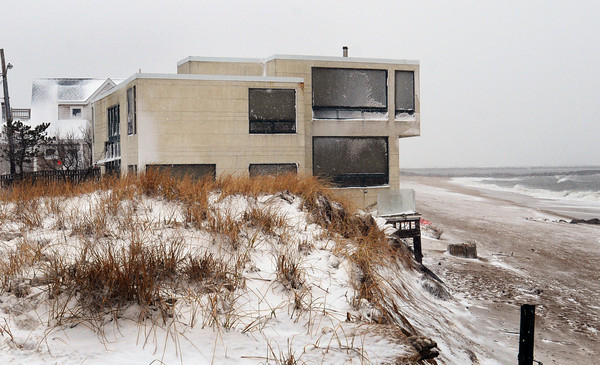 Newburyport: The sand has washed away to the base of this home on 55th Street on Plum Island, owned by Dr. Sadru Hemani. Bryan Eaton/Staff Photo