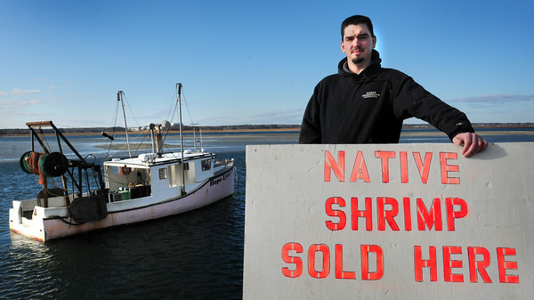 Seabrook: The shrimp boats were idle at Yankee Fisherman's Coop in Seabrook Harbor due to the rough ocean, though days they do land some of the crustaceans, worker Andrew Henderson rolls out this sign onto Route 1A to sell the shrimp. The coop is also promoting the shrimp though its Community Supported Fisheries program. Bryan Eaton/Staff Photo