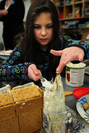 Salisbury: Crista Smith, 8, decorates her tree with frosting which will sit next to her gingerbread house she's making in Michelle Howard's class at Salisbury Elementary School. After counting the pieces of gingerbread and different kinds of candy and creating a graph for a math project, they'll get to  eat their work. Bryan Eaton/Staff Photo