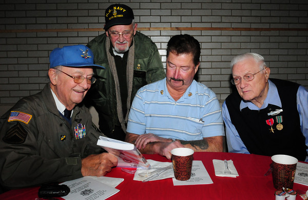 """Amesbury: John Katsaros, left, of Haverhill shows his book, """"Code Burgundy: The Long Escape"""" a true story from World War II in which he served, to fellow veterans Brad Hutchinson, US Navy; Dick Roberts, US Marine Corps and Mike Greaney, US Army Infantry in World War II, all of Amesbury. They were at the annual Amesbury Supports the Troops Christmas dinner at Holy Family Parish Hall last night. Bryan Eaton/Staff Photo"""