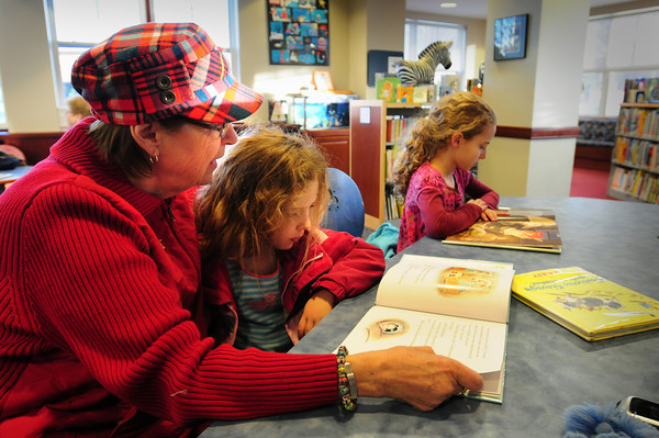 Newburyport: Josephine Kenney reads to Heather Larson, 5, while her sister Katherine, 8, reads a book of her own on Thursday afternoon. They were at the Newburyport Public Library where the Newburyport resident often takes her granddaughters when she watches them. Bryan Eaton/Staff Photo