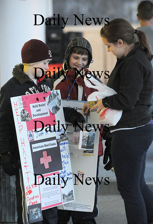 West Newbury: Graham Sampoo, left, and Christopher Yates, center, both in the 4th grade at Page School in West Newbury, receive a donation from Ana Fahey as they pair stands outside of the West Newbury Food Mart Monday night to raise money for Haiti. Photo by Ben Laing/Staff Photo