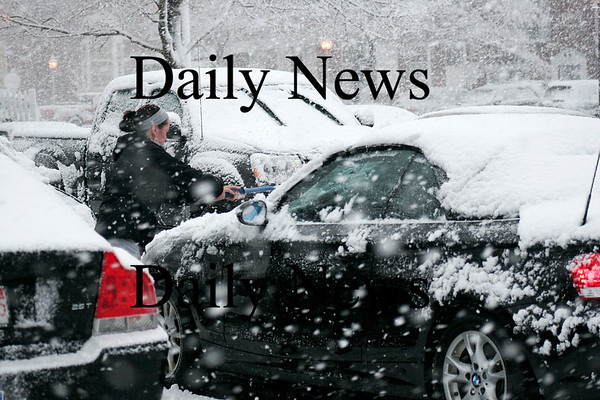 Newburyport: Lori Itszkowitz, owner of Pink Hearts, Blue Soles, a shoe store in Newburyport, cleans off her car in the Green Street lot during Tuesday's late afternoon snow storm. Photo by Ben Laing/Staff Photo