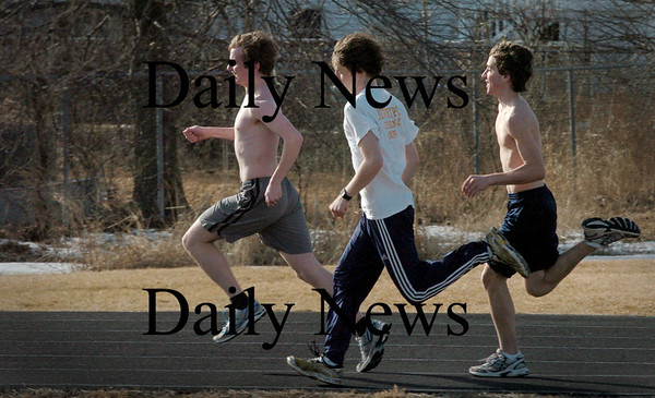 Newburyport: Two of three distance runners on Newburyport High indoor track team were dressed like summertime as they practiced for a state meet on Friday. At Fuller Field on Monday afternoon, from left, John Stansel, Greg Englehart and Chris Suprin. Bryan Eaton/Staff Photo