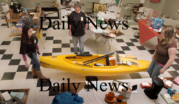 Newburyport: It's all about volunteers helping to ready Opportunity Works' auction this weekend including setting up the items including a kayak. From left, Mariah Crowley, 9, Robin LaPierre, both of Newburyport and Courtney Palma of Lawrence. Bryan Eaton/Staff Photo