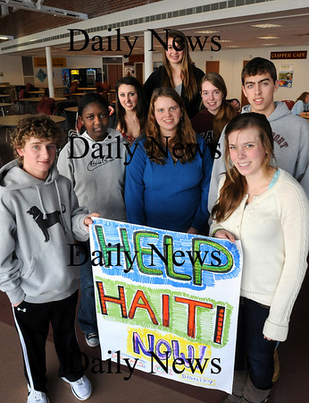Newburyport: Students involved in fundraising for relief efforts in Haiti pose in Newburyport High cafeteria where they are set up. From left, Dylan McCloy, 15, Mellyn Akiny, 16, Alex Haley, 18, Becca Young, (in blue), 16, Gabby Quarantiello, (top), 17, Brittney Perreault, 16, Hannah McCormick, 18, and Harrison Corbett, 15. Bryan Eaton/Staff Photo