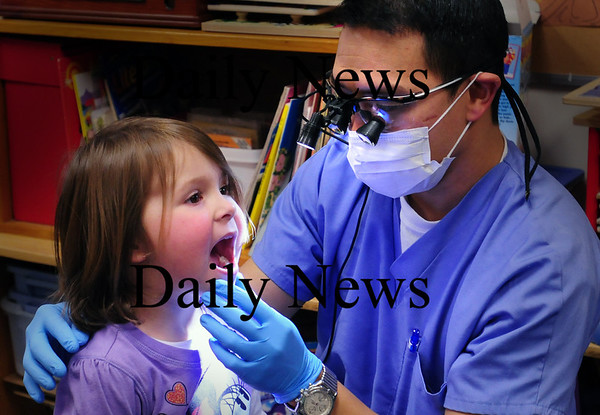 Newburyport: Emma Dollas, 4, opens wide for Dr. Brendan Chiou as he gives a quick check of her teeth as children take turns at Mrs. Murray's Nursery School on Tuesday. The children were learning about the importance of taking care of their teeth. Bryan Eaton/Staff Photo