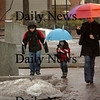 Newburyport: Elisabeth Tollman of Georgetown walks down Inn Street in Newburyport yesterday in the rain with her sons, Alexander, 8, left, and Andrew, 4. They were on their way to do some shopping at the toy store Dragon's Nest. Bryan Eaton/Staff Photo