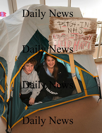 """Newburyport: Dylan McCloy, 15, left, and Gabby Quarantiello, 17, are two of several students at Newburyport High School leading a fund drive for the relief effort in Haiti. One drive was to """"Pitch In"""" money into a bucket set inside this tent in the school's cafeteria and another is the sale of bracelets.  Bryan Eaton/Staff Photo"""