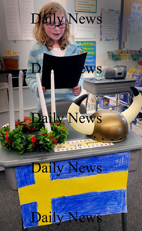 Salisbury: Savannah Miles, 7, reads a piece on Swedish culture with the props of Saint Lucia's crown of candles, the flag and a Norse helmet. Second-graders at Salisbury Elementary School presented Passport for Learning Day where they researched the land of their ancestors and presented to other schoolmates and their parents. Bryan Eaton/Staff Photo