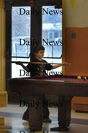 Salisbury: With the snow falling behind him, Rhys Corey, 7, readies for a pool shot. He was playing Jon Burns, 11, at the Boys and Girls Club yesterday afternoon.  Bryan Eaton/Staff Photo