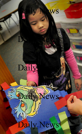 Salisbury: Nina Pham, 6, shows her Chinese dragon to her kindergarten teacher Jane Keeler to check out Tuesday morning. The class are making the dragons for their Chinese New Year celebration on Friday. Bryan Eaton/Staff Photo