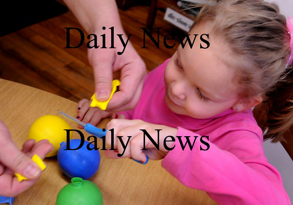 Amesbury: Bailey O'Neil, 5, helps her mother, Katie, cut off then ends of balloons which they stuffed with barley at the Amesbury Public Library's Children's Room on Wednesday. They were filling them up to make juggling balls which the children are going to use to learn to juggle. Bryan Eaton/Staff Photo