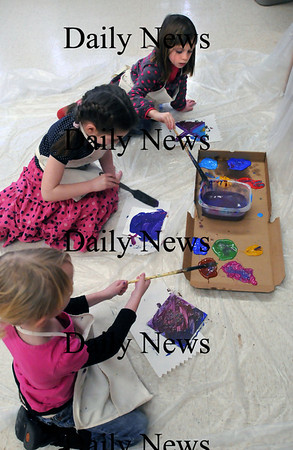 """Newburyport: Brown School students from top, Sadie Riordan, Isabelle Leary and Bella Pessolano, all 6, create abstract art on a ceramic tiles. Sadie's mother, Newburyport artist Lisa Riordan, is organizing a class each from the Brown and Bresnahan Schools to create the works to raise money through an auction for the relief effort """"Save the Children"""" in Haiti. Bryan Eaton/Staff Photo"""