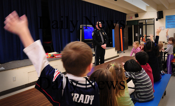 Amesbury: Carson Scarinci, 4, frantically waves his hand as he and fellow preschoolers ask Amesbury police officer Thomas Hanshaw questions after a presentation. The safety topics he talked about ranged from using 911 and being careful with strangers. Bryan Eaton/Staff Photo