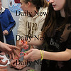 "Amesbury: Ally Gelsomini, 13, left, and Aspen Gibbas, 14, hand out ""friendship bracelets"" during lunchtime at Amesbury Elementary School on Tuesday morning. Each student who signed an agreement for the annual No Name Calling/Bullying Campaign recieve the bracelet. Bryan Eaton/Staff Photo"
