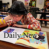 "Amesbury: Isabella Miranda, 10, reads ""The Recess Queen"" at Amesbury Elementary School during the Amesbury Recreation Department's afterschool program. The kids were working on their homework, which Isabella finished and grabbed the book from a rolling bookcart. Bryan Eaton/Staff Photo"