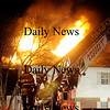 Amesbury: An Amesbury firefighters mans the ladder at the fire on Pamela Lane in Amesbury Friday night. Jim Vaiknoras/Staff photo