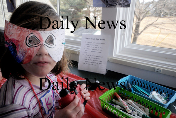 Newburyport: kate Whalen , 4, of Reading, models an eagle mast she made before using her binoculars at the Joppa Center in Newburyport during the annual Eagle Festival Saturday. JIm Vaiknoras/Staff photo