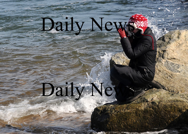 Newbury: Niki Fandel, who is studying photography at Montserrat, gets an up close angle as she takes a few shots of the surf Monday afternoon. Jim Vaiknoras/Staff photo
