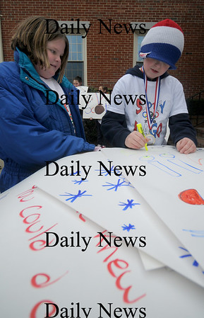 Seabrook:Megan Smith, 9, and Jace Eaton, 11,  of Seabrook make signs  for  Olympian Scotty Lago at a parade in his honor in Seabrook Sunday. Jim Vaiknoras/Staff photo