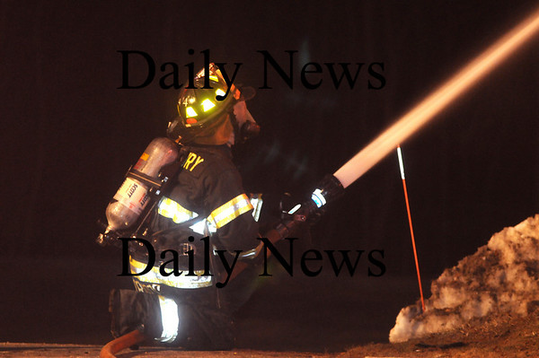 Amesbury: An Amesbury firefighter pours water on the fire on Pamela Lane in Amesbury Friday night. Jim Vaiknoras/Staff photo