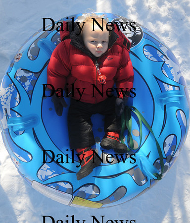 Newburyport: Connor Gibb, 16 month, who is visiting with his family from Shanghai take a break from all the excitment at the Winter Carnival on the Mall in Newburyport Saturday. Hundreds enjoyed a day of skating , sledding, hockey and fun. Jim  Vaiknoras/Staff photo
