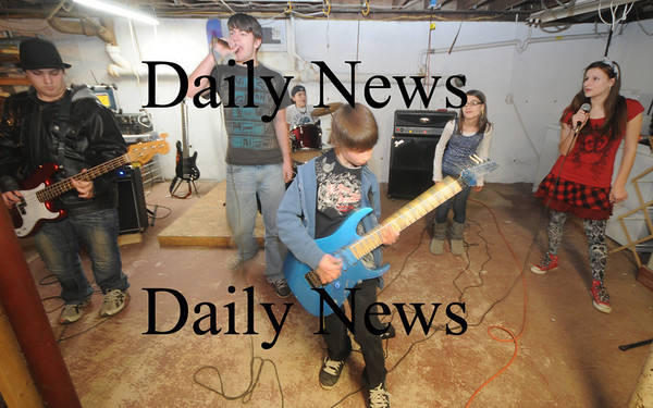 Amesbury: Middle School band Audio Rush rehearses in the Collins' garage in Amesbury. They are Garrett Collins on guitar, Jillian Collins, Aspen Gibbas, and Jacob Myer on vocals, Ryan Collins on bass and Brendon Hanson on Drums. Jim Vaiknoras/Staff photo