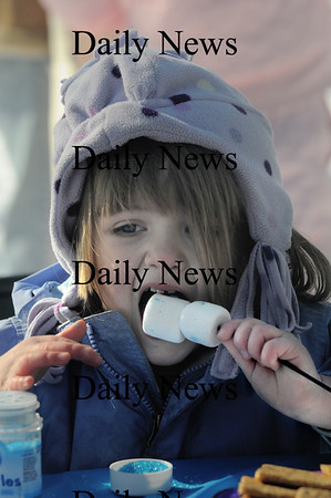 Newburyport: Mallory Iritano, 3, of Amesbury takes a bite out of a marshmallow snow man she make at the Winter Carnival on the Mall Sunday. The snowmen were made with the help of teh Newburyport Mothers ClubJim Vaiknoras/Staff photo