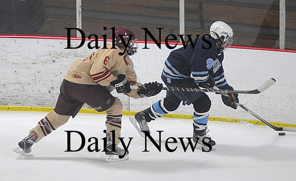 Newburyport: Newburyport's Connor Wile knocks the puck away from Wilmington's Jared Ravagni during their game at the Graf in Newburyport Saturday night. Jim Vaiknoras/Staff photo