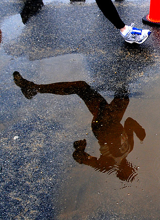 Salisbury: Runners navigate puddles in the Hangover Classic Road Race on Salisbury Beach. Traditionally runners in the race welcome the new year with a swim in the Atlantic. Jim Vaiknoras/Staff photo