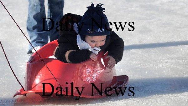 Newburyport: Noah Merrill, 9 month,of Newburyport, hangs on as he is pulled around on a sled by his dad Adam at the Winter Carnival on the Mall in Newburyport Saturday. Jim  Vaiknoras/Staff photo