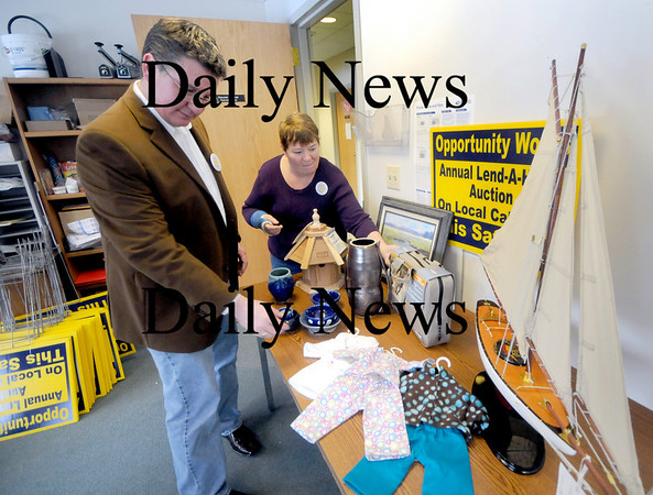 Newburyport: Kathy Eaton and Paul O'Brien look over items that will be auction at the Opportunity  Works auction in February. Jim Vaiknoras/Staff photo