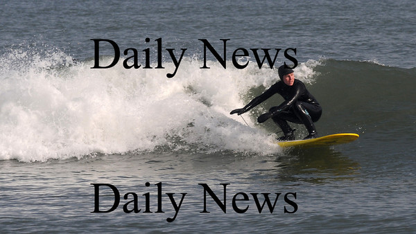 Salisbury: Surfer Kristen Bilodeau takes advantage of the sunny pre-storm weather to ride a wave off Salsibury Beach. Jim Vaiknoras/Staff photo