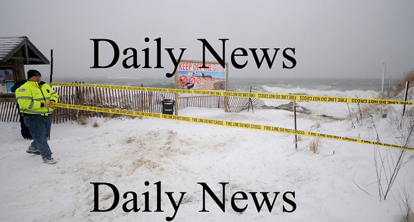 Newbury: Newbury Fireman Robert Bishop runs police tape in the central parking lot on Plum Island to keep people away from the beach at high tide Saturday. The storm and the full moon created high surf in the area. Jim Vaiknoras/Staff photo