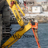 Seabrook:A worker from SPS of Salisbury attatches a line from a crane to a poece of heavy equipment after it tipped over while working on the Hampton River Bridge Friday morning. Jim Vaiknoras/Staff photo
