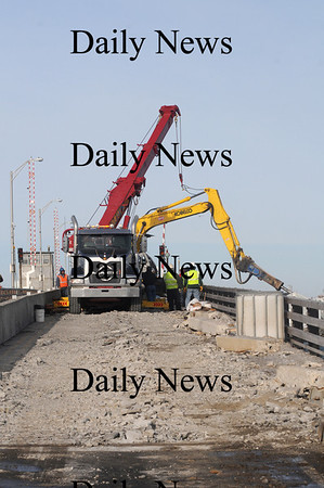 Seabrook: A crane from Coady towing rights a piece of heavy eguipment belonging to SPS of Salisbury after it tipped over while working on the Hampton River Bridge Friday morning. Jim Vaiknoras/Staff photo