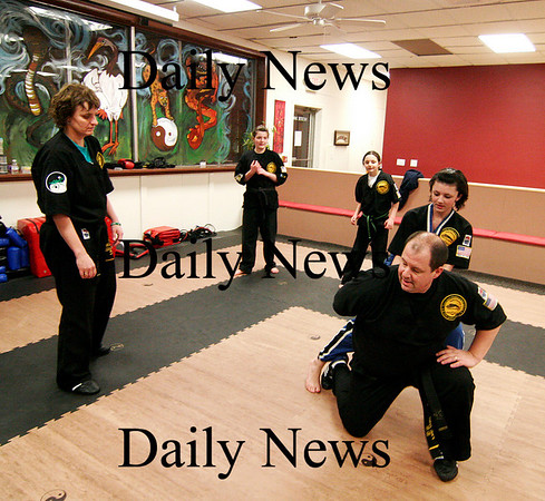 Salisbury: The Poulin family spar Wednesday night at Tokyo Joe's in Salisbury. Joe, the father, is subdued by his oldest daughter Jenna, 14, while his wife Colleen Quinlan, and daughters Kathleen, 13, and Haley, 11, look on. Photo by Ben Laing/Staff Photo