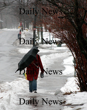 Amesbury: A woman who wished to remain anonymous, struggles with her umbrella against the wind and the rain Monday afternoon as she walks down Friend Street in Amesbury. Photo by Ben Laing/Staff Photo