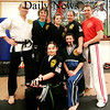 Salisbury: Sensai's Kendall Buhl, left, and Joe Copello, right, stand with the Poulin family, father Joe, center right, mom Colleen, and their three daughters, Kathleen, 13, center, Jenna, 14, bottom right, and Haley, 11. The family have each earned black belts from Tokyo Joe's in Salisbury. Photo by Ben Laing/Staff Photo