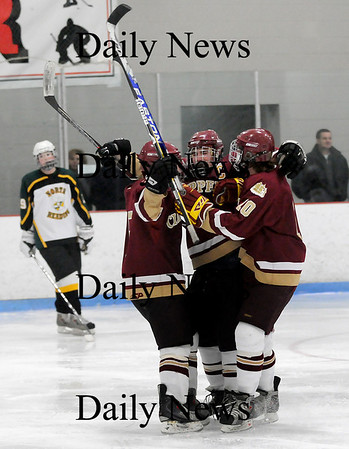 Reading: Kyle McElory, center, is congratulated by teammates Gaven LaValley, left, and Sean Hickman, right, after scoring during Saturday night's 8-3 win over North Reading. Photo by Ben Laing/Staff Photo