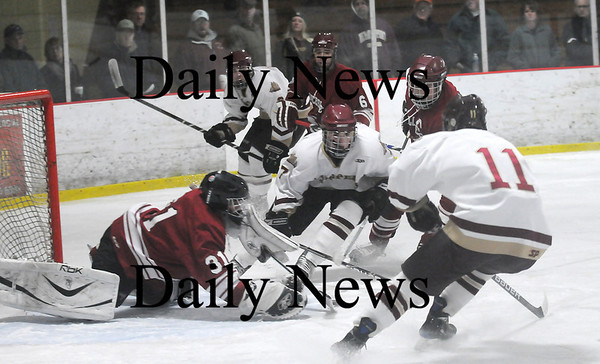 Newburyport: Clippers Gavin LaValley (7) and Ryan Cutter (11) converge on a loose puck in front of the Gloucester net during Monday's game at the Graf Rink. Photo by Ben Laing/Staff Photo