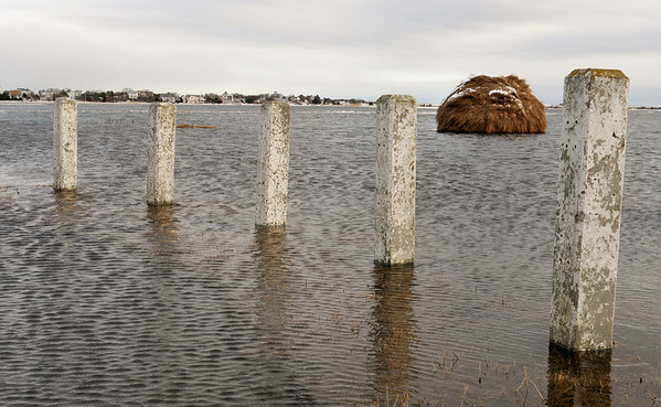 """Newbury: A very high tide surrounds this haystack off the Wilkinson Bridge on the Plum Island Turnpike on Monday afternoon. The stack was built during a Trails and Sails demonstration """"Making Hay in the Sunshine"""" back in the fall/ Bryan Eaton/Staff Photo"""