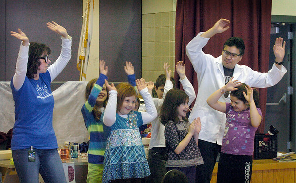 Amesbury: Dr. Will Bartolini and his wife, Kathleen, and a handful of students sway quickly about demonstrating how water molecules would if they were heated, instead of chilled, at the Cashman School in Amesbury on Wednesday morning. The chemist, whose son, Joe, is a second-grader there, did a science presentation teaching about the different states of matter: solid, liquid and gas. Bryan Eaton/Staff Photo