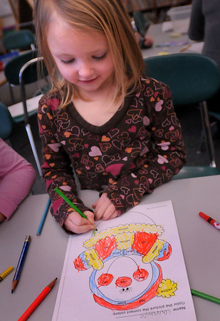 """Salisbury: Cammie Coady, 5, colors in a snowman in Kathleen Orroth's kindergarten class at Salisbury Elementary School on Thursday morning. The children were also cutting out mittens, each having rhyming words, to hang on their mural """"The Rhyming Clothesline."""" Bryan Eaton/Staff Photo"""