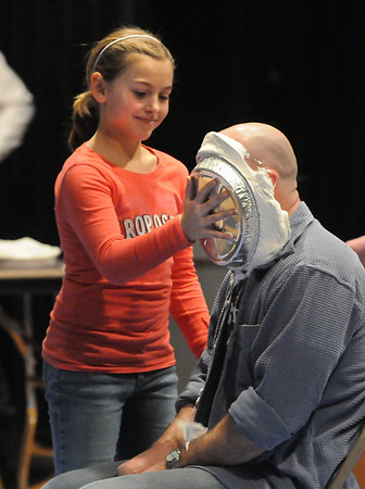 Amesbury: Emma Richardson, 10, slams a whipped cream pie onto teacher Mike Wesolowski at Amesbury Middle School for a fundraiser for the school  band Friday afternoon. Bryan Eaton/Staff Photo