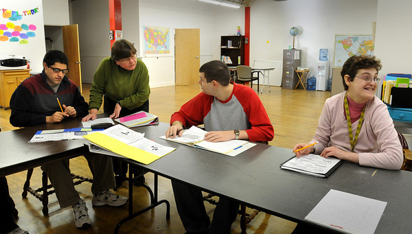 Amesbury: Instructor Jane Hinckley works with students in math at Coastal Connections new location at Bartley Machine in Amesbury's Lower Millyard. From left, Ben Younger, Hinckley, Nate Pouliot and Kris Knowles. Bryan Eaton/Staff Photo