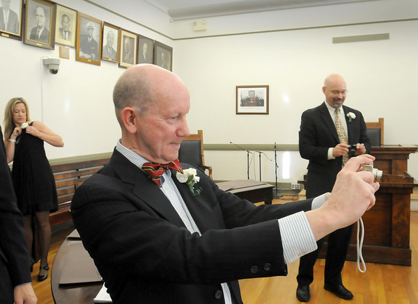 Newburyport: Newburyport City Clerk Richard Jones takes a photograph of Mayor-Elect Donna Holaday, with the nine living former mayors, before swearing her in later. Bryan Eaton/Staff Photo