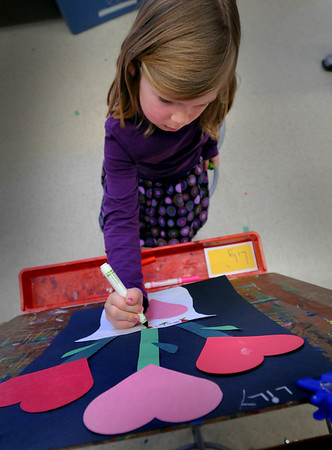 Newburyport: Lily Pflaum, 5, decorates the pot of a planter sprouting Valentine hearts that she cut out in Pam Jamison's art class at the Brown School on Wednesday afternoon. The kindergartner will be taking their project home to hang on their refrigerators in time for Valentine's Day. Bryan Eaton/Staff Photo